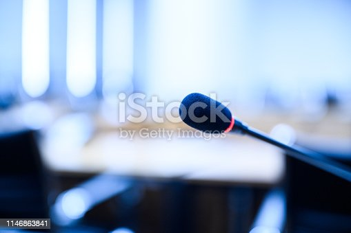 814301186istockphoto Microphone over the blurred business forum Meeting or Conference Training Learning Coaching Room Concept, Blurred background. 1146863841