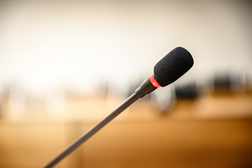831720990 istock photo Microphone over the blurred business forum Meeting or Conference Training Learning Coaching Room Concept, Blurred background. 1146863900