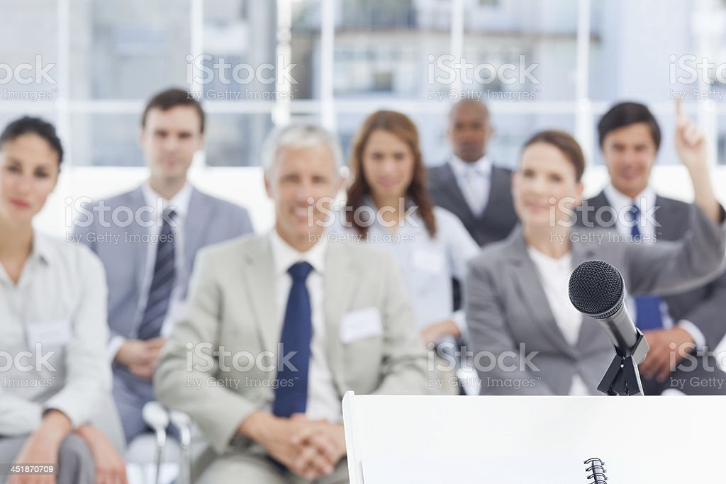 Microphone placed on a stand in front of business people Microphone placed on a stand in front of a businesswoman that has a query as she sits with her colleagues with focus on the microphone 20-29 Years Stock Photo