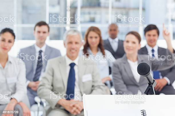 Microphone Placed On A Stand In Front Of Business People Stock Photo - Download Image Now
