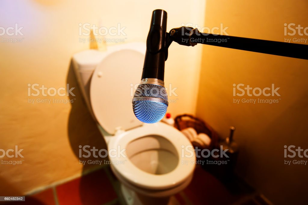 Microphone pointing at toilet in bathroom stock photo