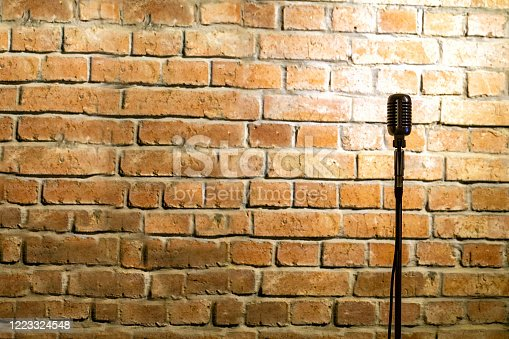 Microphone ready on stage against a brick wall