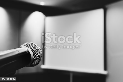 821463698istockphoto microphone ready to use in the podium and the projector screen on the back of the meeting room for the press conference. selective focus. black and white photo. 901963662