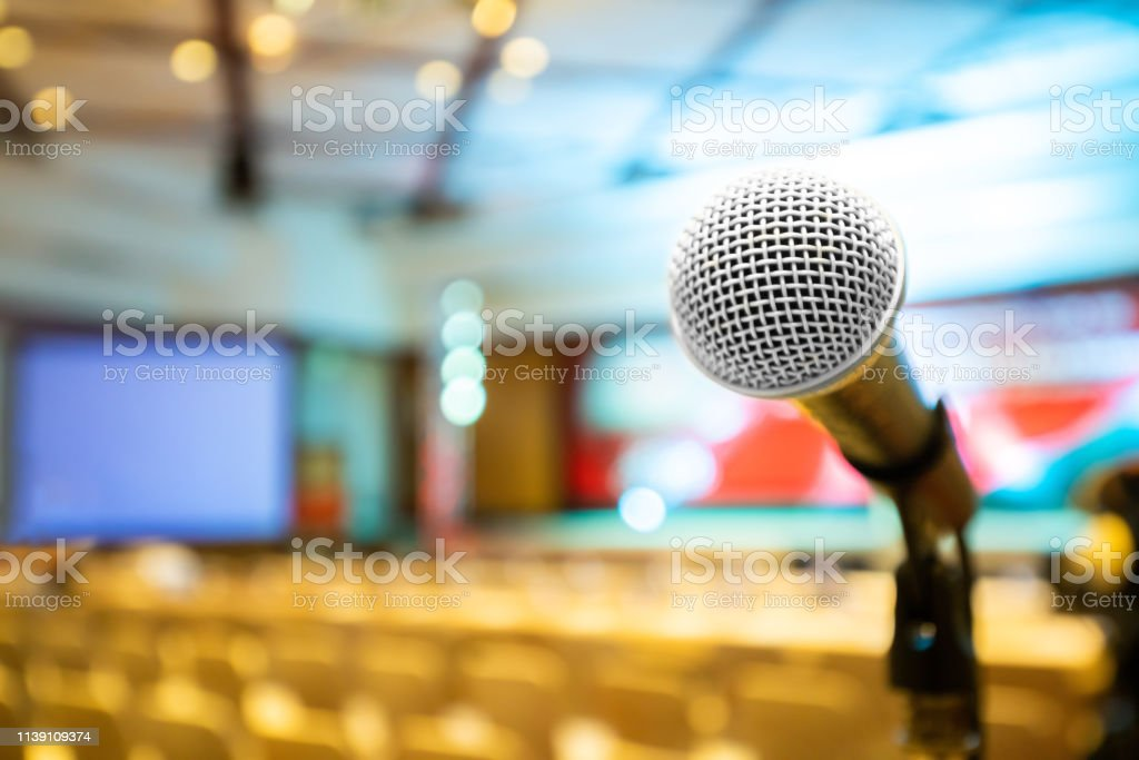 Microphone stand abstract blurred photo in conference hall or seminar...