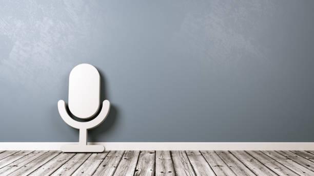 Símbolo do microfone no chão de madeira contra a parede - foto de acervo