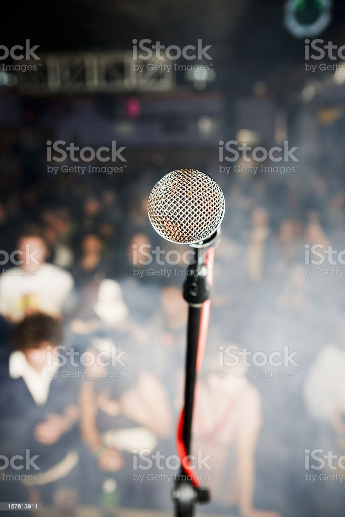 Microphone viewed from stage towards out-of-focus audience royalty-free stock photo