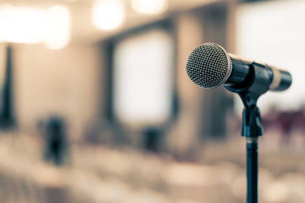 Microphone voice speaker in business seminar, speech presentation, town hall meeting, lecture hall or conference room in corporate or community event for host or public hearing Microphone voice speaker in business seminar, speech presentation, town hall meeting, lecture hall or conference room in corporate or community event for host or public hearing town hall stock pictures, royalty-free photos & images