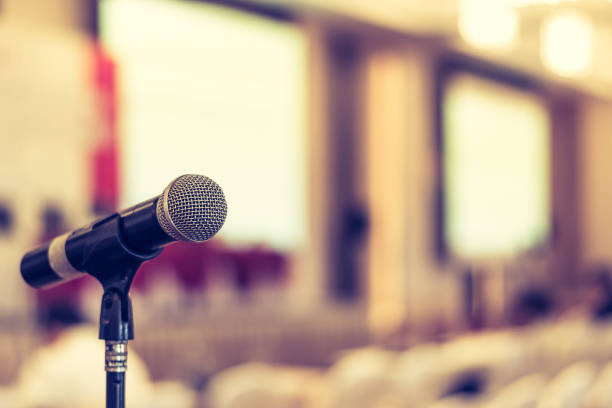 Microphone voice speaker in business seminar, speech presentation, town hall meeting, lecture hall or conference room in corporate or community event for host or townhall public hearing stock photo