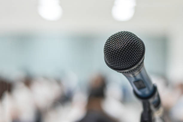 Microphone voice speaker with audiences or students in seminar classroom, lecture hall or conference meeting in educational business event for host, teacher, or coaching mentor stock photo