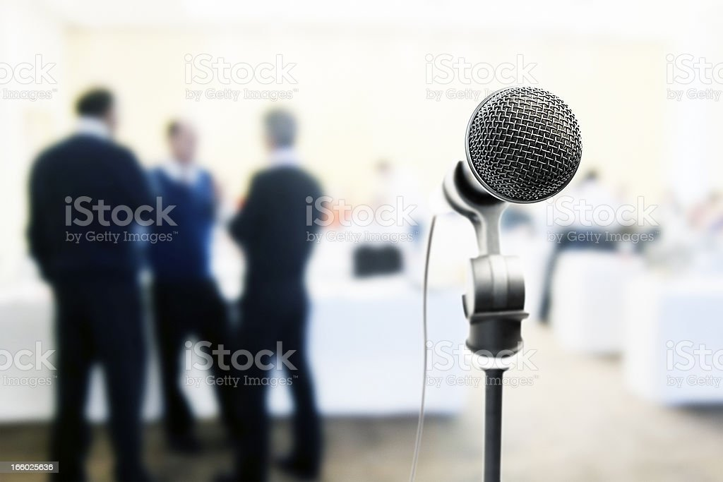 Microphone waits for speaker at meeting; male attendees stand behind royalty-free stock photo