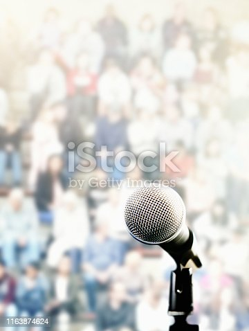 A microphone on a stand in front of a large, defocused audience.