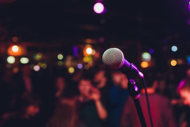 Mikrofon mit verschwommenem, bunten hellen Licht im dunklen Nachthintergrund, weiches Fokusbild für Business-Technologie-Kommunikationskonzepte. – Foto