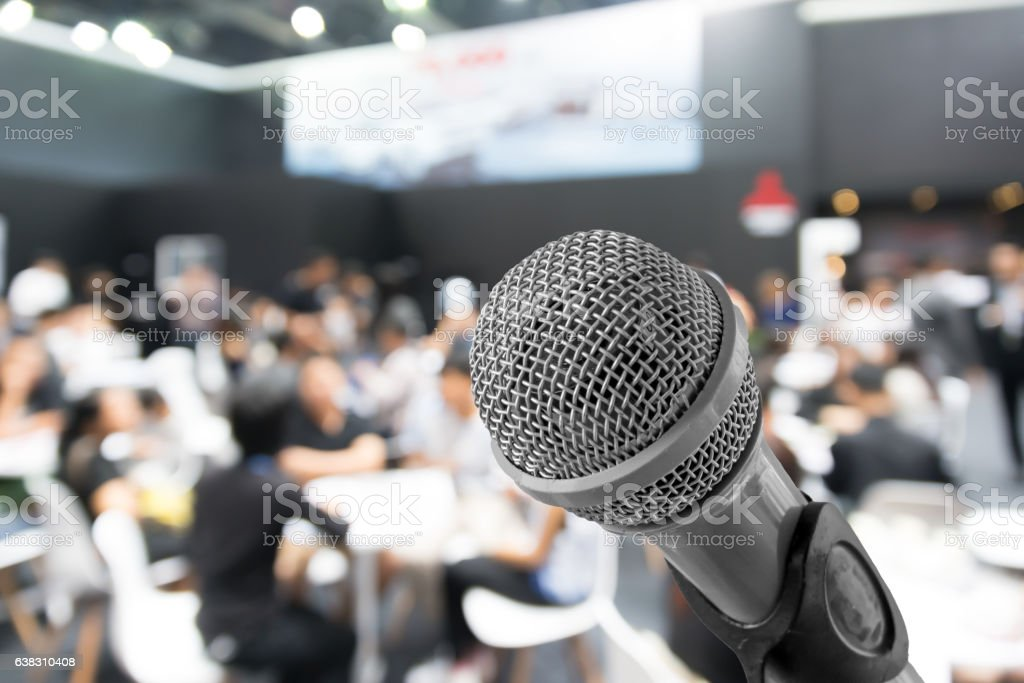 Microphone with blurred photo of conference hall or seminar room stock photo