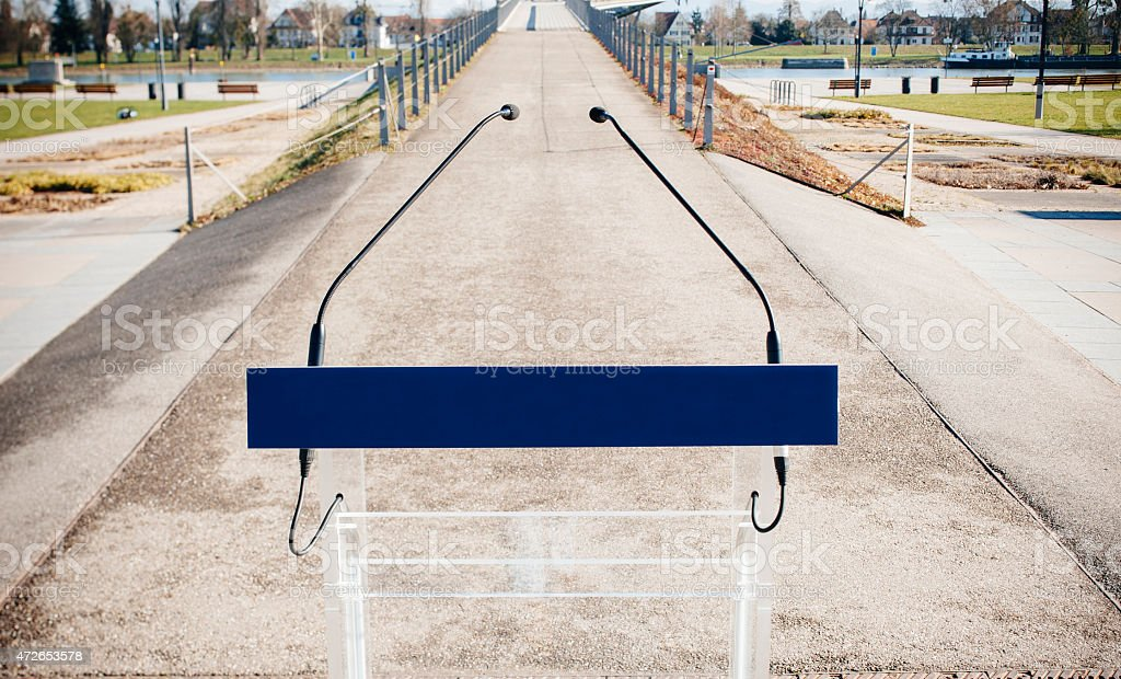 Microphones on lectern outside with defocused view bridge stock photo