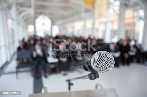 671733994 istock photo Microphones on the funeral podium and people wearing black in the church 1085833516