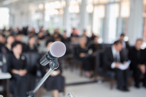 istock Microphones on the funeral podium and people wearing black in the church 1085833518