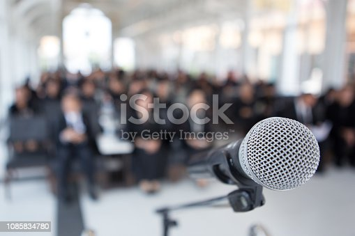 671733994 istock photo Microphones on the funeral podium and people wearing black in the church 1085834780