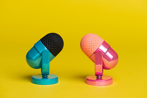 Two microphones facing each other. One microphone is pink the other microphone is blue on yellow background. Representing a discussion between male and female arguments.