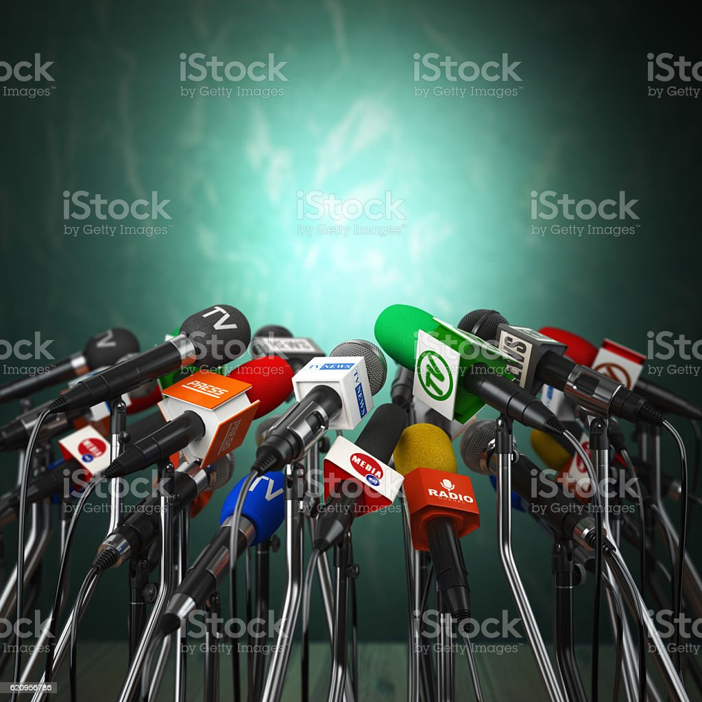 Microphones prepared for press conference or interview on green stock photo