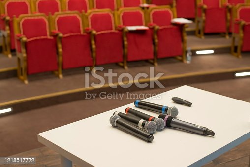1028234706 istock photo Microphones prepared for speakers at a business conference. 1218517772