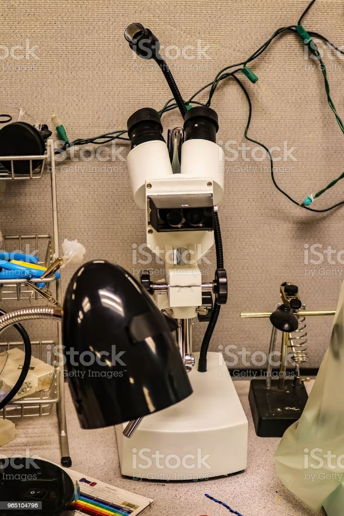 Microscope on desk in electronics lab with  other equipment sitting around it. zbiór zdjęć royalty-free