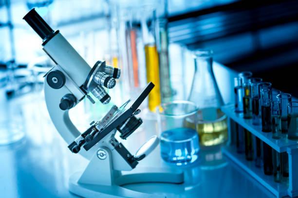 microscope on the table with chemical tube and glassware in laboratory - ricerca scientifica foto e immagini stock