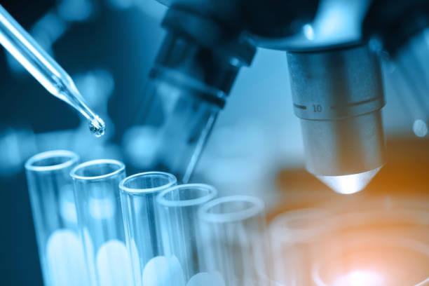 microscopio con cristalería de laboratorio - química fotografías e imágenes de stock