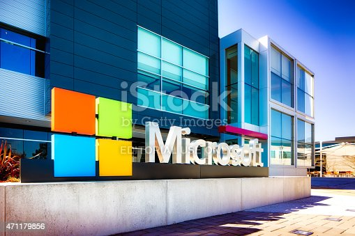 Mountain View, USA - March 4, 2015: Microsoft sign at the entrance of their Silicon Valley campus in Mountain View, California. One of the main buildings can be seen in the background. Oblique view.