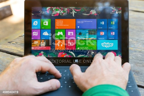 Ankara, Turkey - September 8, 2013:  Man using his surface tablet at the park. Microsoft Surface is a series of tablets designed and marketed by Microsoft