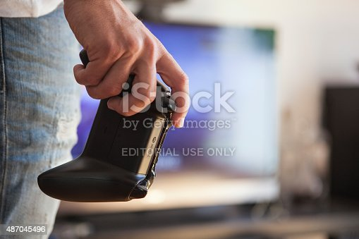 Gothenburg, Sweden - June 21, 2015: A shot of a young man's hand holding a Xbox One game controller, a remote controller for the Xbox One video game console developed and released by Microsoft in 2013. Natural lighting. Shot in a home bedroom during the day with a TV in the background.