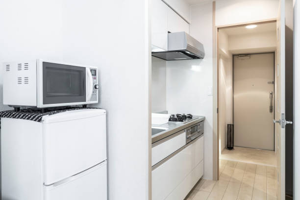 Microwave and refrigerator placed next to the kitchen cabinet in a small new apartment room stock photo