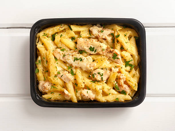 microwave dinner -chicken and penne alfredo - gemaksvoedsel stockfoto's en -beelden