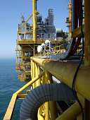 View along the side of offshore oil production platform showing microwave communication dishesMore offshore rig images: