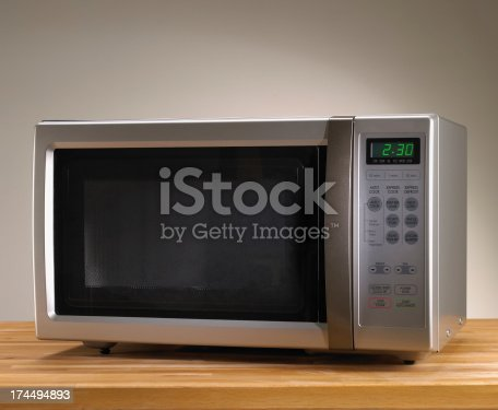 Microwave oven on wooden table with time displayed