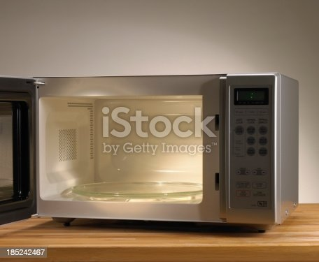 Microwave oven open on wooden table