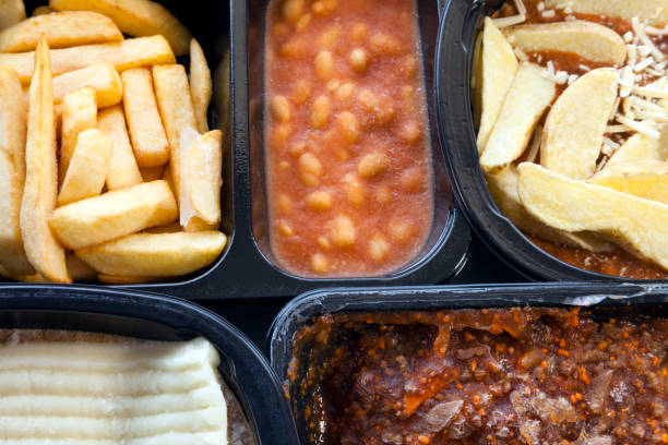 Microwaveable, ready to eat meals of chips, mince,beans, lasagna, in black plastic boxes, still unfrozen . stock photo