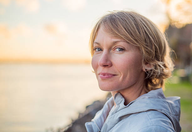 Mid 30's Woman with strong smile at sunset. Blonde, short hair, blue eyed, mid 30's woman gives a strong contented smile as the sun sets behind her. 30 34 years stock pictures, royalty-free photos & images