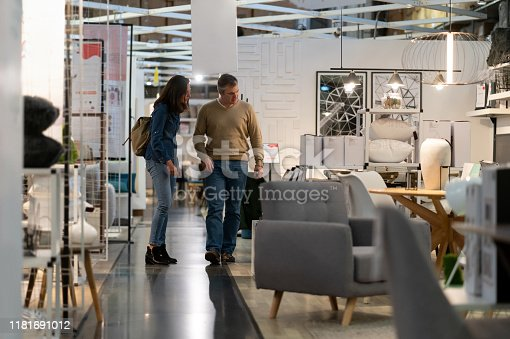 Mid adoult couple walking at a furniture store while talking and smiling - Consumerism concepts