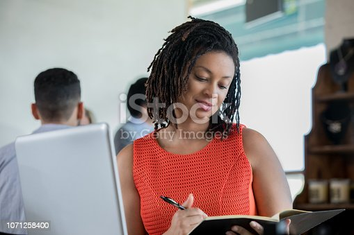 694187664 istock photo Mid adult African American female is studying or working in a coffee shop 1071258400