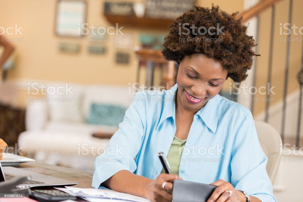 Mid adult African American woman balances checkbook in home office stock photo
