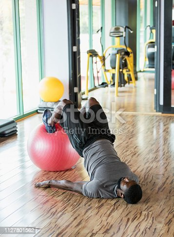 istock Mid adult African-American man working out at gym 1127801562