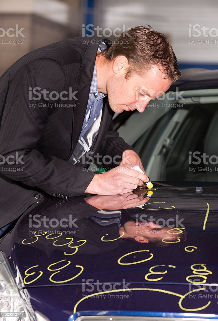 Mid adult appraiser looking at car, estimate for fix stock photo