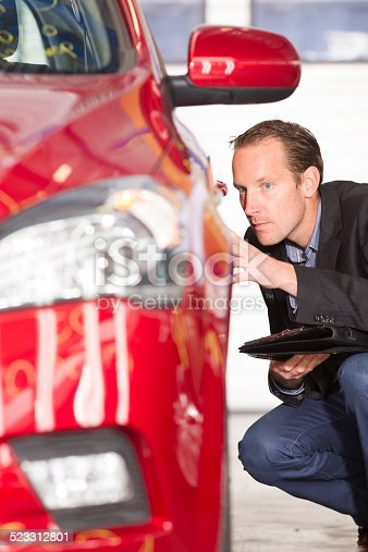 istock Mid adult appraiser looking at red car, estimate for fix 523312801