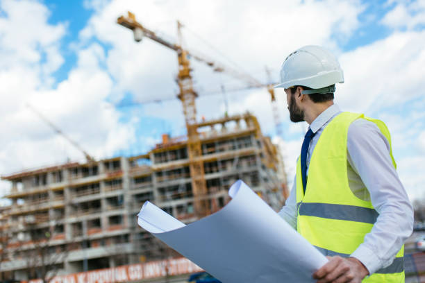 Mid adult architect looking toward construction site stock photo