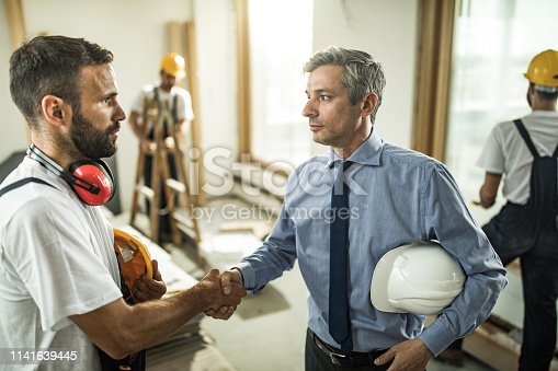 961745166istockphoto Mid adult architect shaking hands with manual worker at construction site. 1141639445