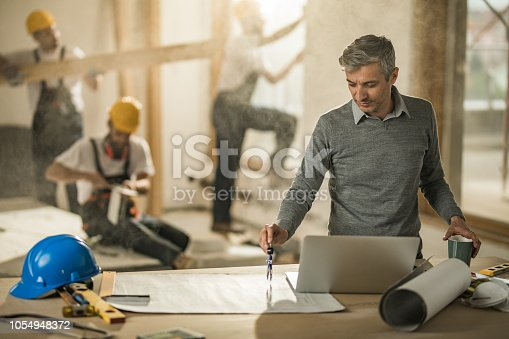 891274328 istock photo Mid adult architect using drawing compass on blueprints at construction site. 1054948372
