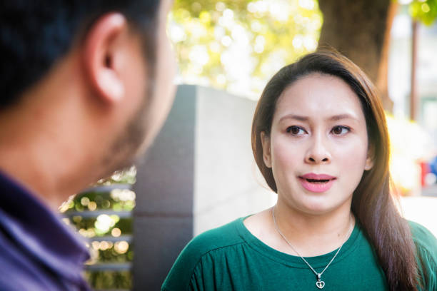 mid adult asian female offended by male remark - bad date stock photos and pictures
