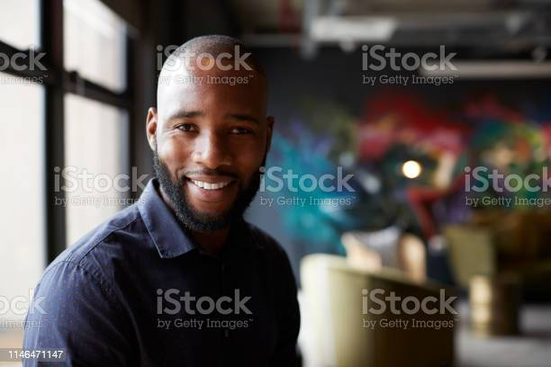 Mid adult black male creative in an office social area turning to picture id1146471147?b=1&k=6&m=1146471147&s=612x612&h=ookbgsgzo d2vdubfbdvyee2ycomzbeporclxwknkao=