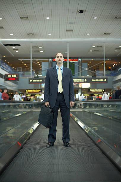 Mid adult business man carrying briefcase at airport stock photo
