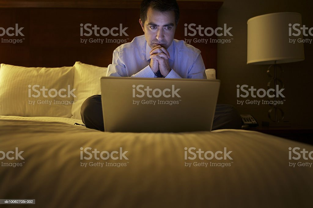 Mid adult business man sitting on bed in hotel room working on laptop royalty-free stock photo